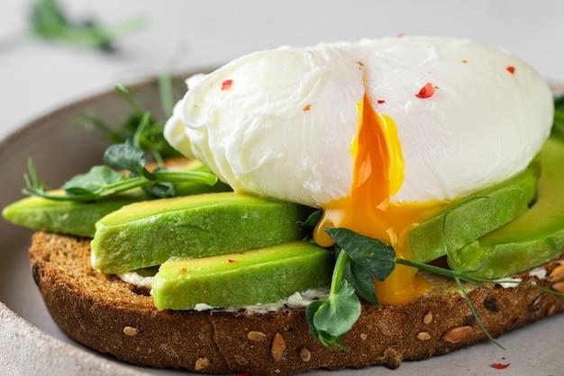 Pane integrale tostato con avocado, uovo in camicia, germogli di piselli e formaggio