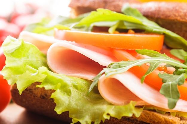 Panino integrale con prosciutto, pomodoro, lattuga e rucola con bicchiere di succo d'arancia. colazione