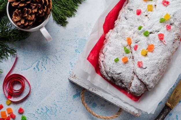Stollen integrale con uvetta e zucchero a velo su tovagliolo di lino con setaccio, nastro rosso sul cemento azzurro nevoso