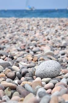 Whote ciottoli ia spiaggia con blu mare sullo sfondo