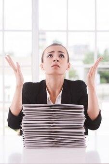 Perché io? depressa giovane donna in tuta che guarda in alto e gesticola mentre è seduta al tavolo con una pila di documenti posati su di esso