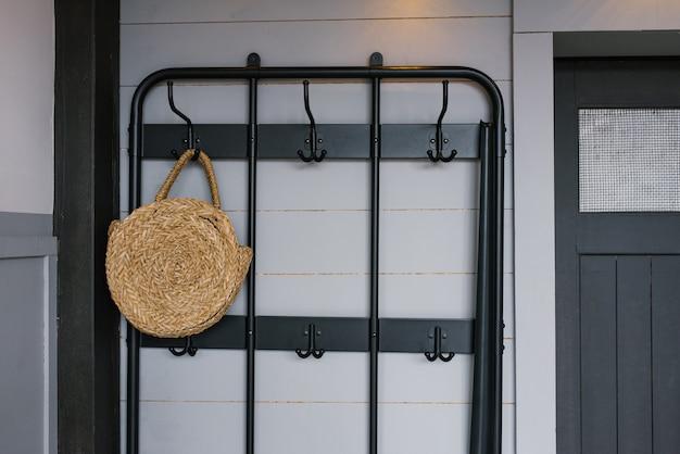 Una borsa di vimini è appesa a una gruccia vicino alla porta d'ingresso all'interno di una casa scandinava
