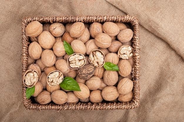 Un cesto di vimini riempito con noci intere e sbucciate con foglie di basilico svehu su un tessuto marrone naturale