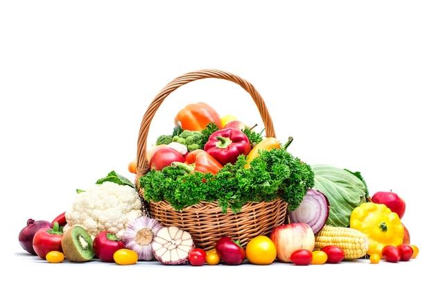 Cesto di vimini pieno di frutta e verdura biologica isolata