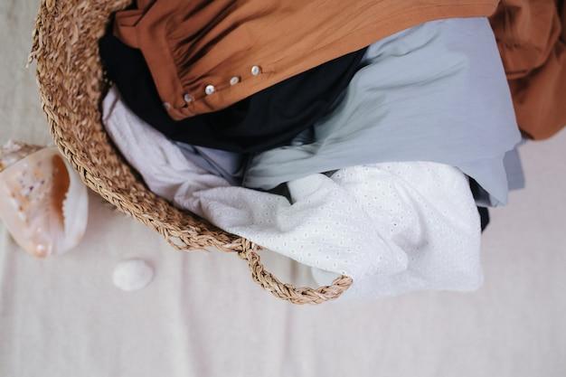 Cesto di vimini pieno di abiti estivi per lavare la biancheria. vista dall'alto.