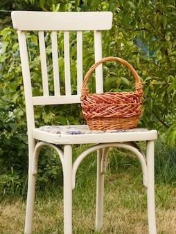 Cestino di vimini sulla vecchia sedia in sfondo naturale. attrezzi da giardino.