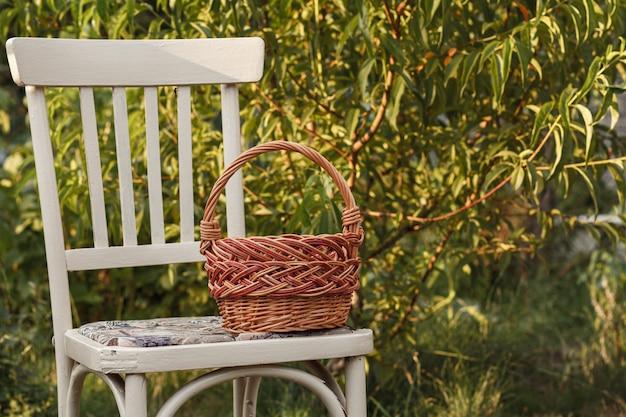 Cestino di vimini sulla vecchia sedia sullo sfondo naturale. attrezzi da giardino.