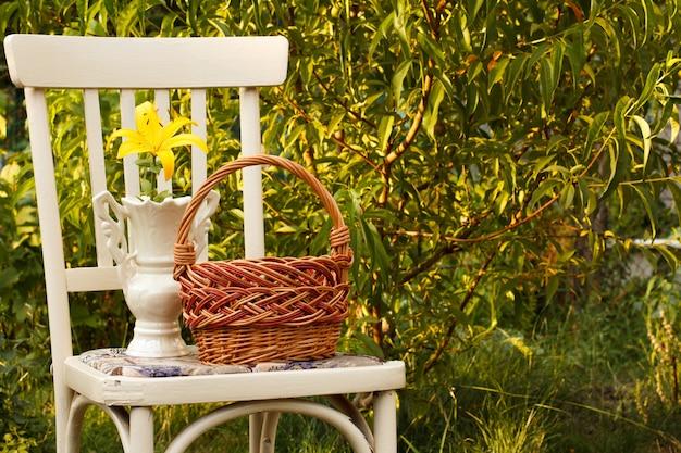Cesto di vimini e vaso con fiori di giglio sulla vecchia sedia in sfondo naturale. attrezzi da giardino.