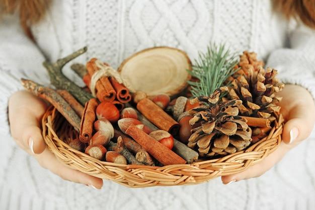 Cesto di vimini con decorazioni natalizie nelle mani di una donna, primo piano