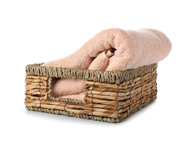 Cestino di vimini con asciugamano morbido pulito su superficie bianca