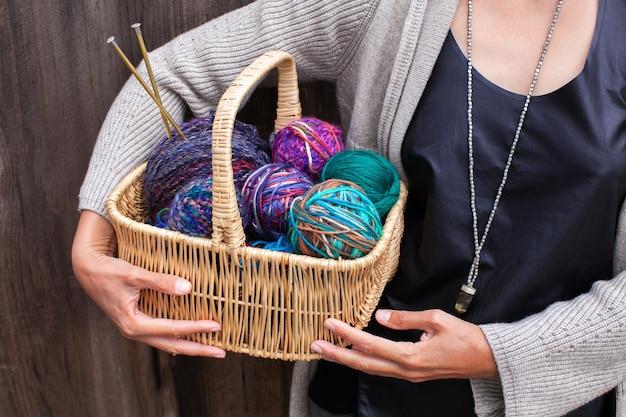Cesto di vimini con palline luminose colorate di filato di lana per lavorare a maglia in mani femminili.