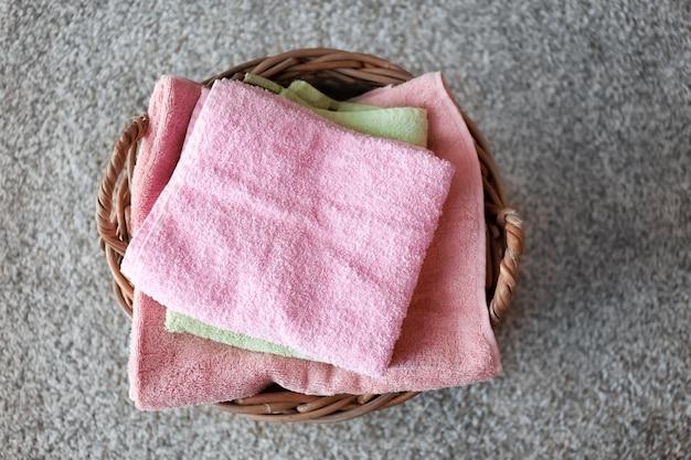 Cesto di vimini con asciugamani puliti piegati sul pavimento