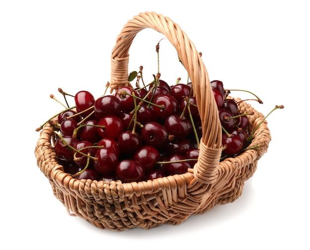 Cestino di vimini con ciliegie mature su sfondo bianco