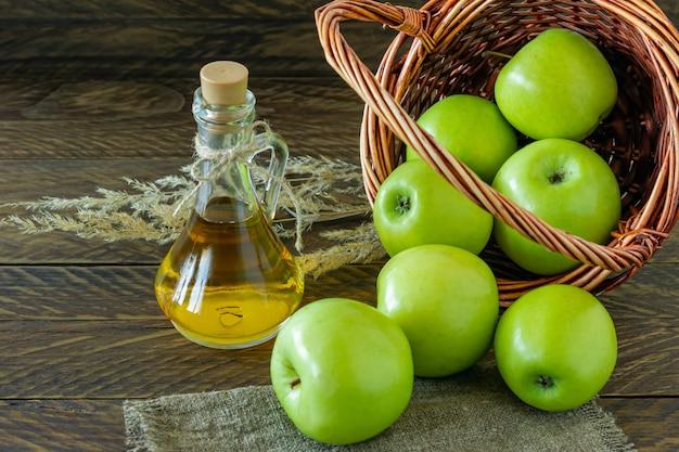 Cestino di vimini con mele verdi mature e bottiglia di aceto di mele su fondo di legno.