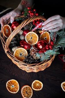 Cesto di vimini con bastoncini di zucchero a strisce, arance essiccate a fette, coni e regali.