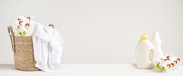Cesto di vimini con biancheria bianca, gel detergente e ammorbidente su un tavolo bianco con fiori di orchidea. giorno della lavanderia dell'intestazione del modello con lo spazio della copia.