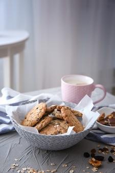 Ciotola di vimini con deliziosi biscotti di farina d'avena e tazza di caffè sul tavolo