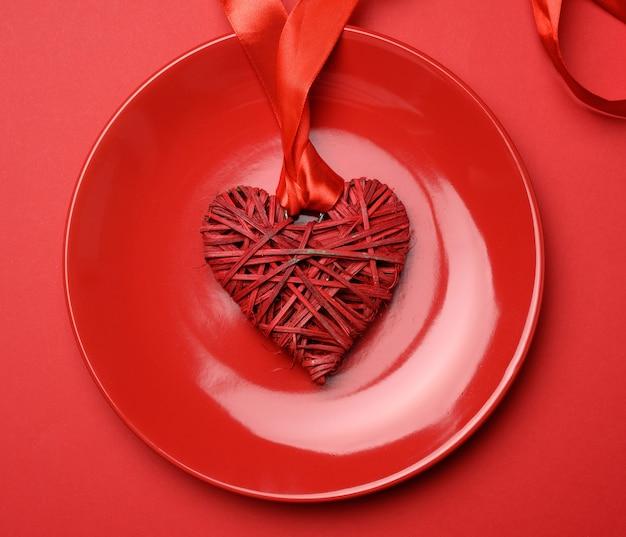 Cuore di vimini in un piatto in ceramica rossa, vista dall'alto