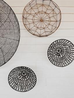 Decorazioni orientali ornamentali in vimini su parete bianca