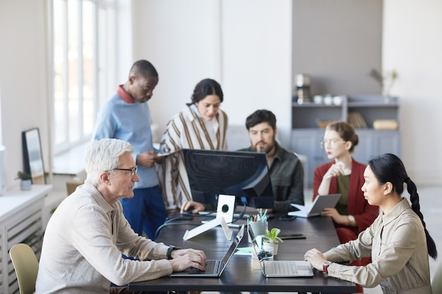 Ampio angolo di diversi gruppi di uomini d'affari che si incontrano in ufficio e usano il computer mentre discutono del progetto