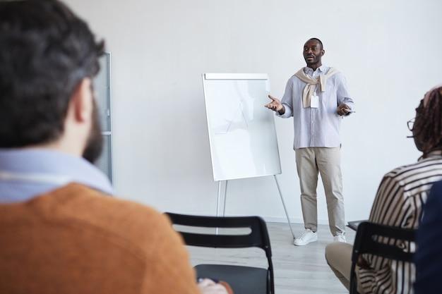 Ritratto grandangolare di business coach afro-americano che parla con il pubblico alla conferenza o al seminario educativo mentre è in piedi vicino alla lavagna e gesticola, copia spazio
