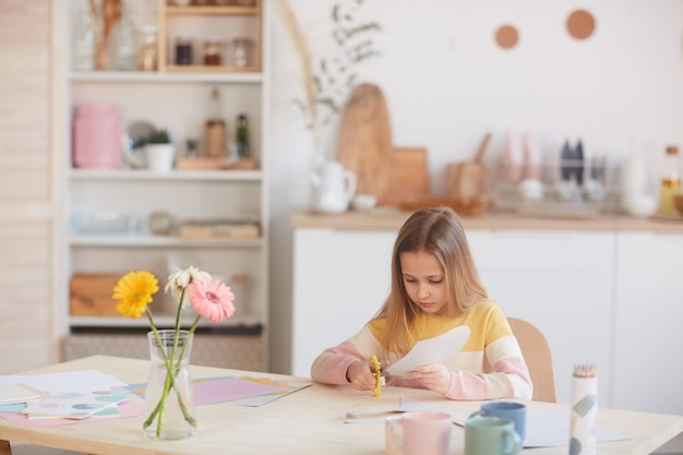 Ritratto grandangolare della ragazza sveglia che taglia carta di festa fatta a mano per la festa della mamma o il giorno di san valentino mentre è seduto al tavolo con i fiori, lo spazio della copia