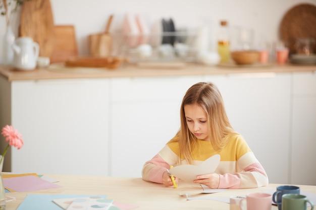 Ritratto grandangolare della ragazza carina che fa la carta di vacanza per la festa della mamma o il giorno di san valentino mentre è seduto al tavolo in interni domestici accoglienti, spazio di copia