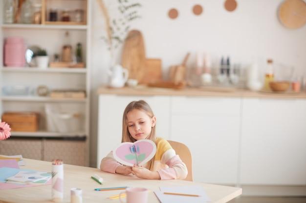 Ritratto grandangolare della bambina sveglia che tiene carta a forma di cuore mentre era seduto al tavolo in interni domestici accoglienti, spazio di copia