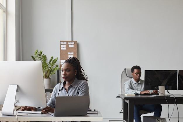 Ritratto grandangolare di due giovani afro-americani che utilizzano computer mentre lavorano in un ufficio di sviluppo software, copia spazio