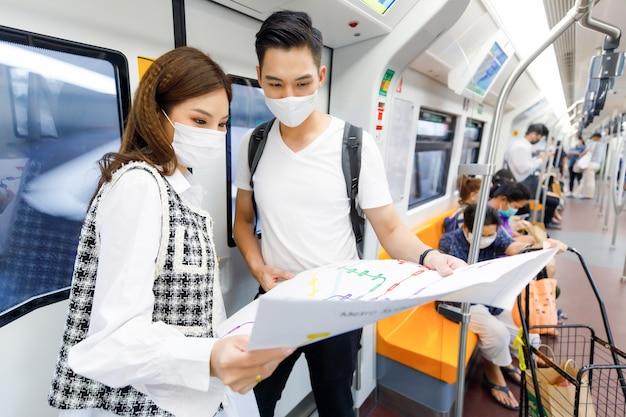 Ritratto grandangolare di giovani viaggiatori asiatici adulti con una maschera medica in piedi e tenendo insieme la mappa cartacea della metropolitana nello skytrain con uno skytrain sfocato e un gruppo di persone sullo sfondo