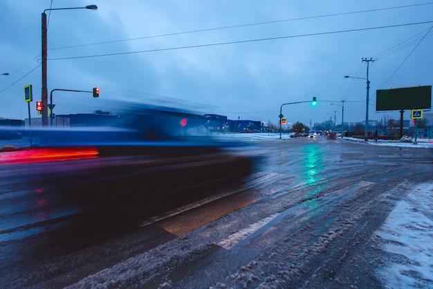 Colpo grandangolare di un'auto in movimento su una strada cittadina in una sera d'inverno. traffico auto in movimento nella stagione fredda.