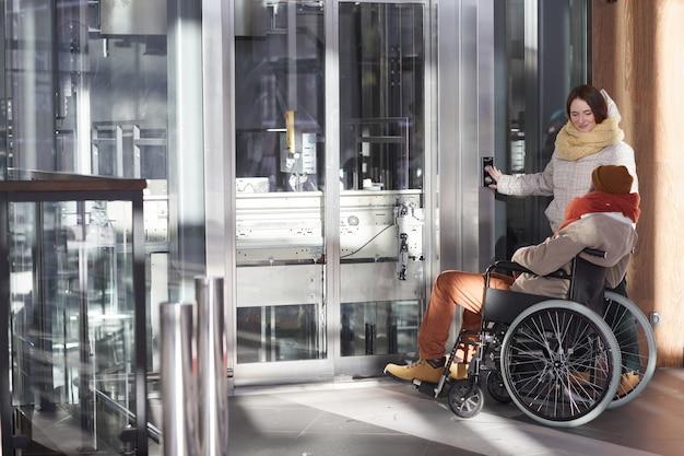 Vista grandangolare all'uomo afroamericano in sedia a rotelle che utilizza l'ascensore accessibile con la giovane donna che assiste, spazio della copia