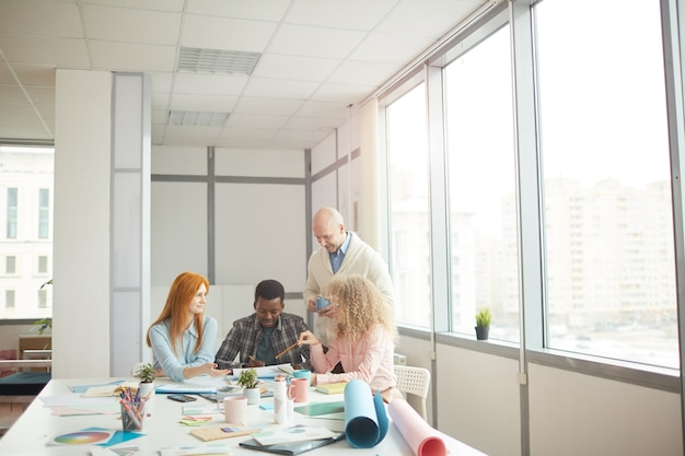 Ampio angolo di visione a diversi business team discutendo progetto creativo durante la riunione al tavolo in un moderno ufficio bianco, copia dello spazio