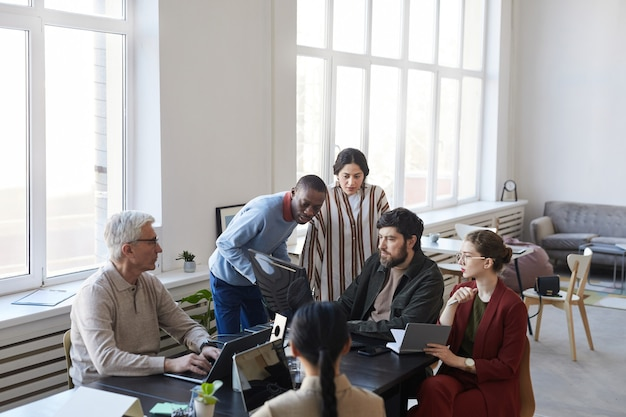 Ampio angolo di visione a diversi gruppi di uomini d'affari che si incontrano in ufficio e usano il computer mentre discutono di progetti, copia spazio