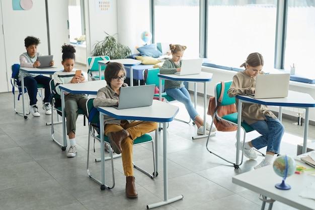 Vista grandangolare su un gruppo eterogeneo di bambini piccoli che usano gadget mentre sono seduti ai banchi in aula scolastica, copia spazio