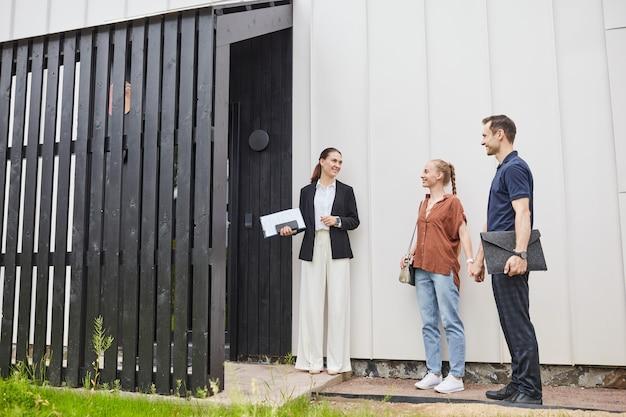 Vista grandangolare all'agente immobiliare femminile che incontra una giovane coppia da una casa minima in design scandinavo in bianco e nero, spazio di copia