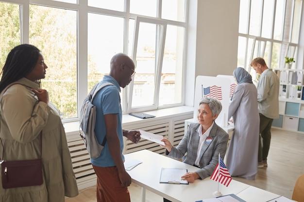 Ampio angolo di visione al gruppo multietnico di persone che si registrano per votare al seggio elettorale decorato con bandiere americane, copia dello spazio