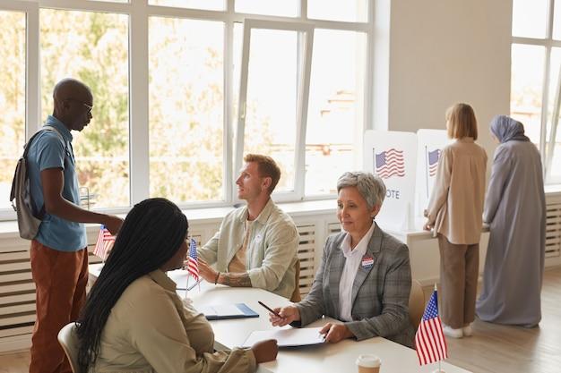 Ampio angolo di visione al gruppo multietnico di persone che votano al seggio elettorale decorato con bandiere americane, copia dello spazio