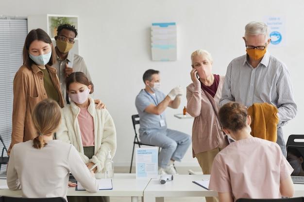 Ampio angolo di visione delle persone in attesa in fila durante la registrazione per il vaccino covid nel centro medico, copia spazio
