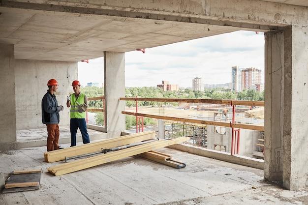 Vista grandangolare a due operai edili che indossano elmetti protettivi mentre si trovano in cantiere, copia spazio