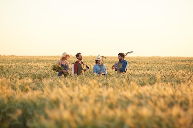 Ampio angolo di visione ai lavoratori che tengono gli strumenti mentre si cammina attraverso il campo dorato nella luce del tramonto, copia dello spazio