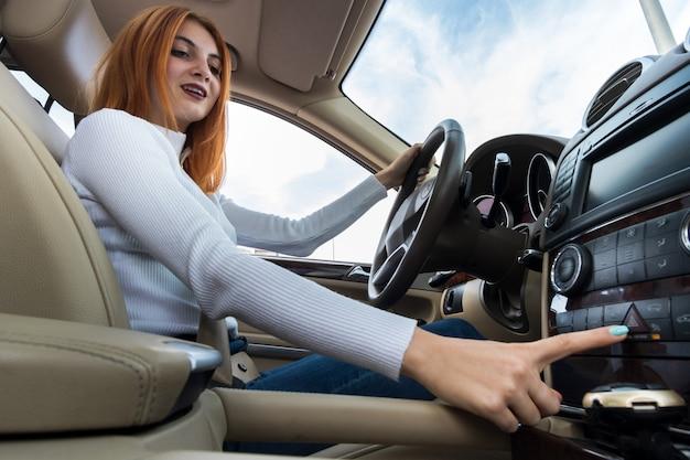 La vista grandangolare di giovane autista della donna di redhead si è fissata dalla cintura di sicurezza che conduce un'automobile che sorride felicemente.