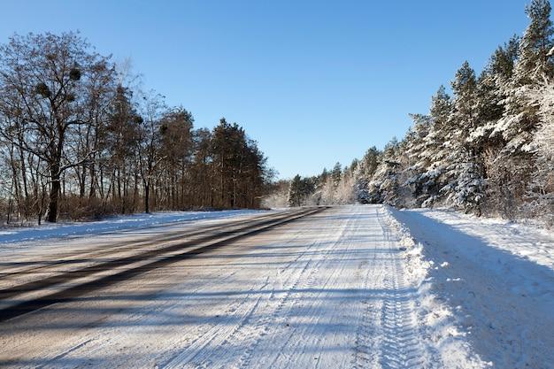 Ampia strada asfaltata, su cui sono presenti solchi di auto sulla carreggiata, nella foresta nella stagione invernale, cielo blu sullo sfondo Foto Premium