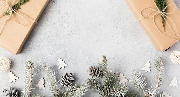 Ampio sfondo di natale con regali, rami di abete, coni e neve sul tavolo di cemento grigio. formato panoramico per banner, copia spazio