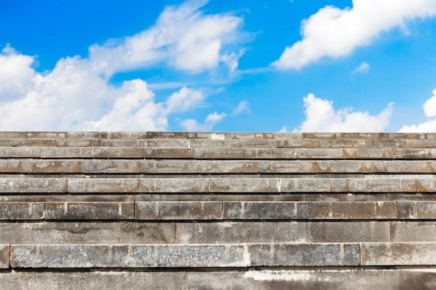 Gradini larghi in cemento grigio, progettati per il traffico pedonale. avvicinamento. sullo sfondo il cielo con le nuvole