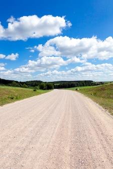 Un'ampia strada di campagna contro un cielo azzurro con nuvole. ai lati della strada crescono mais e bosco