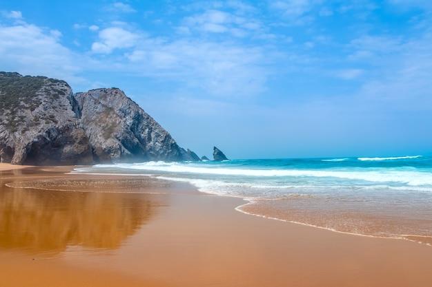 Ampia spiaggia dorata sulle rive dell'oceano atlantico. costa rocciosa e surf. cielo blu