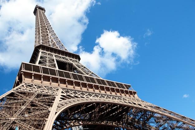 Ampia vista di angolo basso della torre eiffel che guarda verso l'alto nel cielo blu, spazio della copia