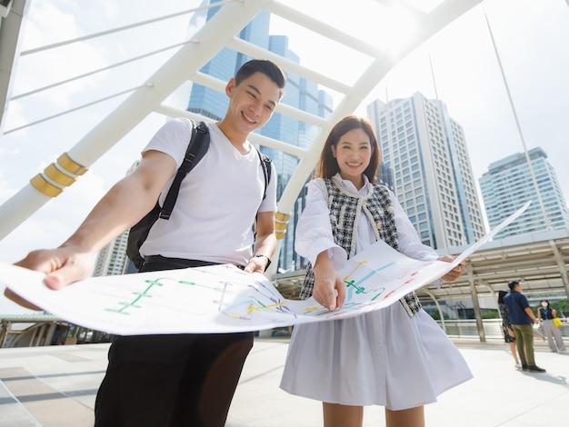Ampio angolo di visione ritratto di sorridente giovane amante felice un viaggiatore asiatico in piedi e guardando la mappa della metropolitana di carta insieme alla donna che indica la mappa per trovare la stazione di destinazione con la mappa sfocata in primo piano