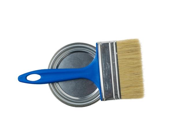 Un pennello largo e un barattolo di vernice chiuso sono isolati su una superficie bianca. materiali per la pittura.